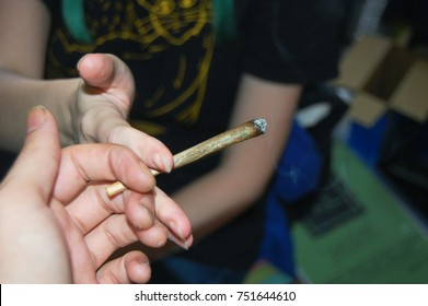 Two people passing a joint