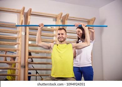 two people, physiotherapy, physiotherapist correcting patient back, arms raised, holding bar. upper body shot.
