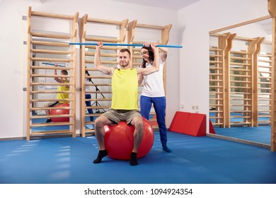 two people, physiotherapy, physiotherapist correcting patient back, arms raised, holding bar. full lenght shot.