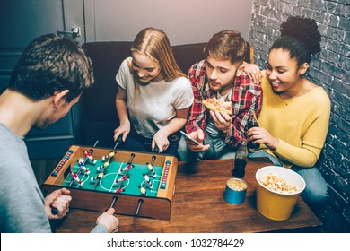 Two people are playing football board game on the table while another two are watching on it and trying to support players as best as they can. Nobody knows who will win