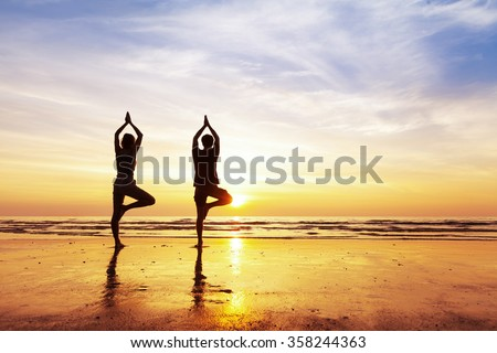 Two people practicing yoga tree position on the beach with beautiful sunset and reflection