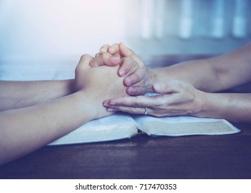 Two  people are praying together over holy bible on wooden table