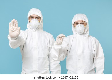 Two people in protective suits respirator masks hold in hand thermometer isolated on blue background studio. Epidemic pandemic new rapidly spreading coronavirus 2019-ncov, medicine flu virus concept