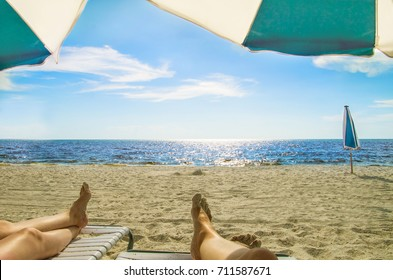 Two people relax on an empty beach by a calm blue ocean during vacation in Naples, Florida