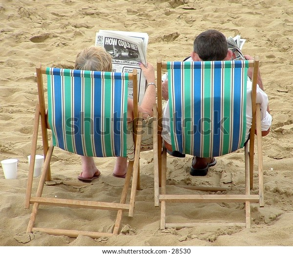 Two people relaxing in deckchairs at the beach.