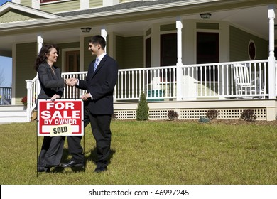 """Two people shake hands as they place a """"for sale"""" sign in front of a house. This could be two realtors who have sold the house or a realtor and buyers."""
