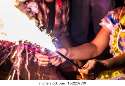 two people sharing sparklers that are lit and shooting sparks in the air