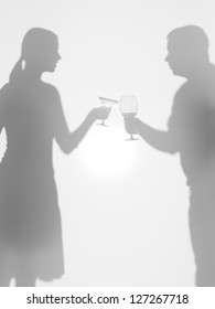 two people silhouettes holding two different glasses, behind a diffuse surface, cheers