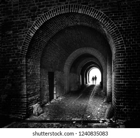 two people silhouettes are walking together like a couple through an old dark brick tunnel to the light, future concept in black and white