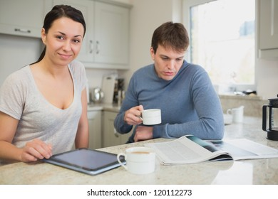 Two people sitting in the kitchen reading news and drinking coffee