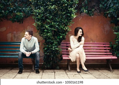 Two people sitting on different benches looking to opposite sides
