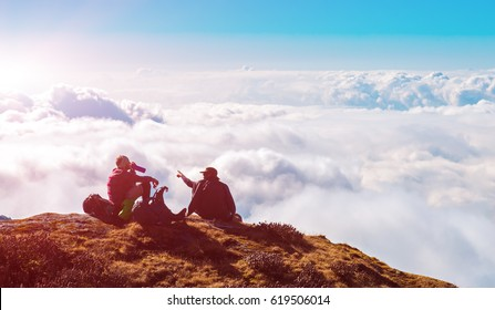 Two People sitting on high Cliff above clouds in Mountains relaxing after challenging Hike in Himalaya
