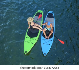 two people sitting on stand up paddle boards from a top overhead view