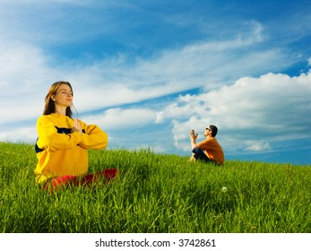 Two people sitting in an open field of green grass on a bright sunny day; meditating.
