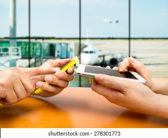 two people with smart phones at the airport connecting with wifi