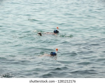 Two people snorkeling in sea water at Ko Kut, Trat, Thailand. Picture shows back of heads and air tubes above water