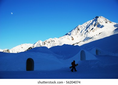 Two people with snowboards walking in mountains