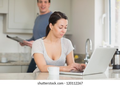 Two people spending time in the kitchen while using the laptop and reading a magazine