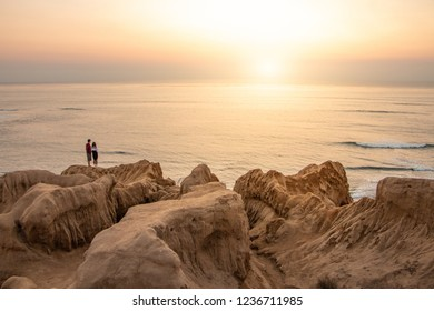 Two people stand in the distance looking towards a sunset over the ocean.  Interesting cliffs and rocks lead the eye towards the couple and towards the hazy sunset.