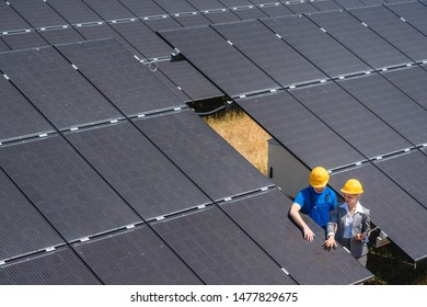 Two people standing amid solar cells in a power plant inspecting the modules