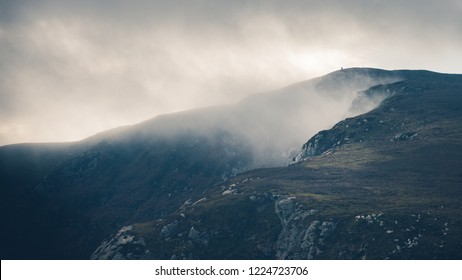 Two people standing far away on the top of the misty hill in Wicklow Mountains National Park, Ireland.