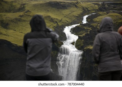two people are standing in front a skyfall in Iceland (I specifically focused on the waterfall to underline its power