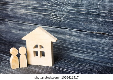 Two people are standing near the house. Wooden figures of persons stand near a wooden house. The concept of a couple in love, cohabitants, parents, buyers and sellers at home. They live in the house.