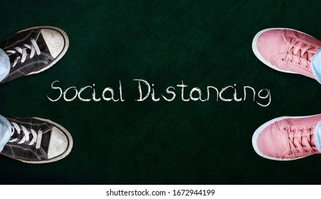 Two people standing on chalkboard with the word social distancing in between. Concept of staying physically apart for infection control intended to stop or slow down the spread of COVID-19 conoravirus