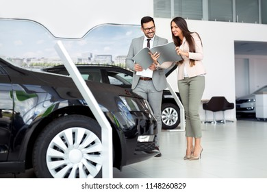 Two people talking about car contract in car salon