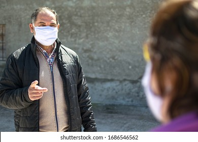 Two people talking keeping security distance, wearing protection mask for coronavirus or covid-19 virus outbreak in a city. Corona virus, Covid-19, virus outbreak or social distancing concept