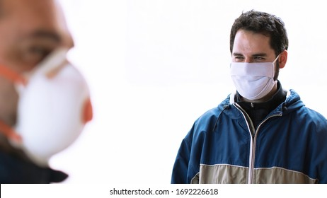 Two people talking keeping security distance, wearing protection mask for coronavirus or covid-19 virus outbreak in a city. Corona virus, Covid-19, virus outbreak or social distancing concept.