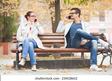 Two people talking on the phones in a park