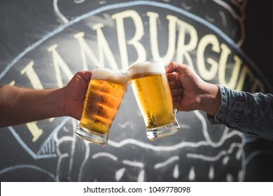 two people toasting with two chopp mugs, celebration, to the bottom wall with the hamburger writing, in the photo appear only the hands of the people.