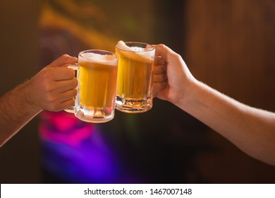 Two people toasting with mugs full of chopp