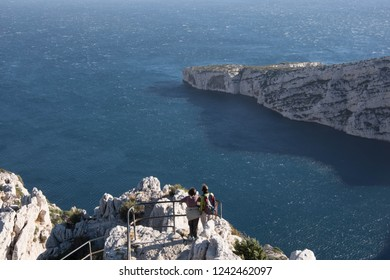 two people of the traveler are standing against the backdrop of the incredible scenery of the bay Calanque in Marseille in France. blue sea and sheer white rock. Parc National des Calanques