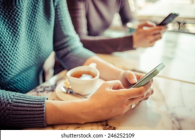 Two people using smart phones in cafe. Toned picture