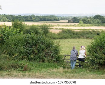 Two people viewed from behind, one wearing a hat ,lean on an old gate looking at a countryside scene stretching into the distance with hedgerows and fields on a beautiful sunny day.