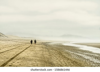 Two people walk along the deserted foggy beach early in the morning at Cape Kiwanda Oregon in Pacific City