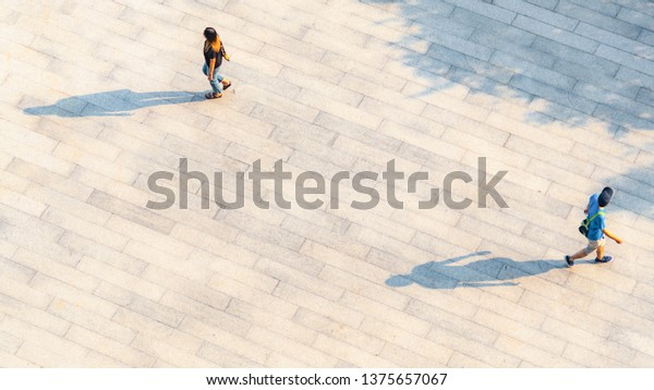 two people walk converse on across the pedestrian concrete landscape with black silhouette shadow on ground (top aerial view)