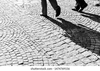 Two people walk together on a cobblestone street, their long shadows cast in the harsh sunlight.
