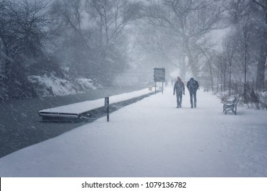 Two people walking along canal in the snow during the Beast from the East, Edinburgh, Scotland.