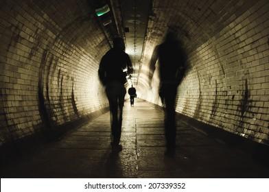 Two people walking in the dark tunnel