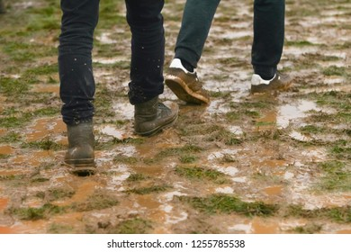 Two people walking in the mud.