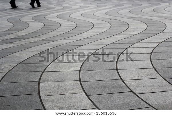 Two people walking on a beautiful Wavy Tile Patterns in Canary Wharf, London
