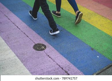 two people walking on lgbt colored crosswalk in urban setting