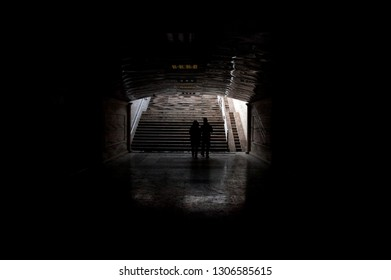 Two People walking towards the exit of an Underground Pedestrian Tunnel