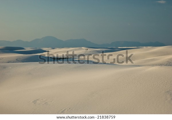 Two people walking in the vast gypsum dunes of White Sands National Monument in southern New Mexico.