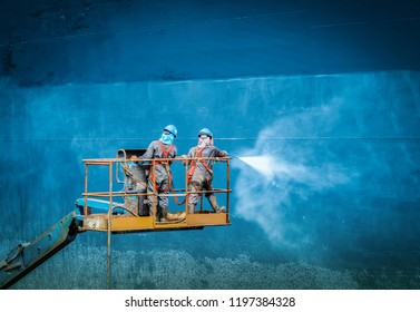 Two people washing ship, Work in floating dry dock with water jet cleans the shipboard and have movement of people of the ship from sea vegetation before sandblast and paint