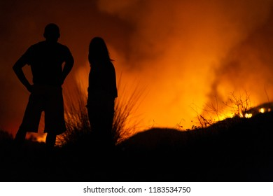 Two people watch wildfires at night