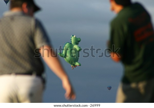Two people watching hot air balloons